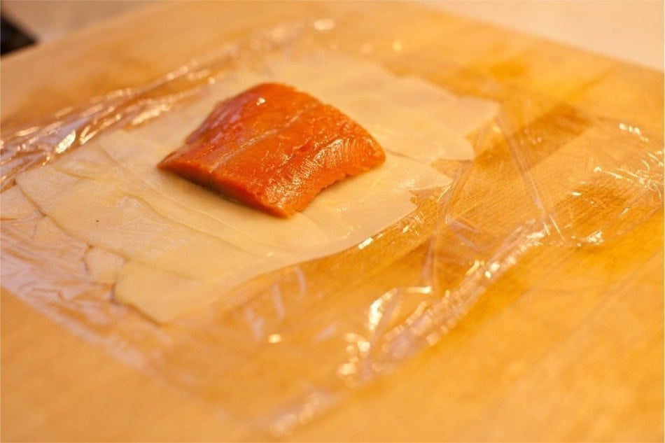 Using plastic wrap, you can wrap the potato slices around the salmon.